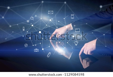 Male hands touching interactive table with blue mixed communication icons in the background #1129084598