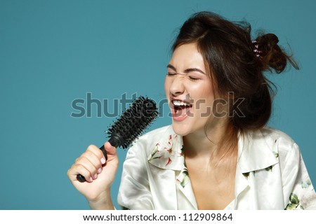 Cheerful attractive teen girl sing song holding comb like a microphone in the morning. Over blue background.