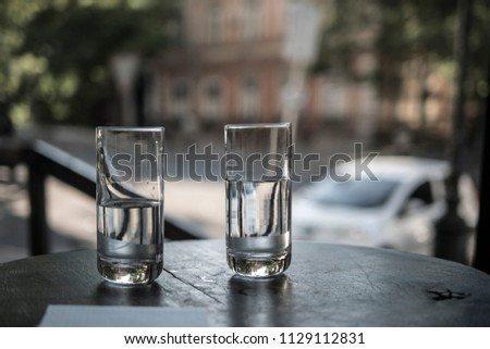 Two glasses of water stand on a table in a restaurant on the background of city streets #1129112831