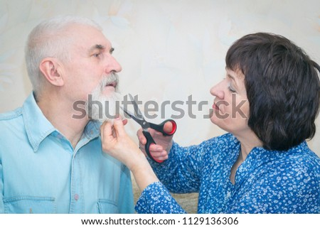 Portrait of an elderly couple. The wife cuts her husband's beard with scissors. #1129136306
