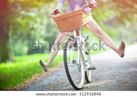 Woman riding bicycle with her legs in the air #112916848
