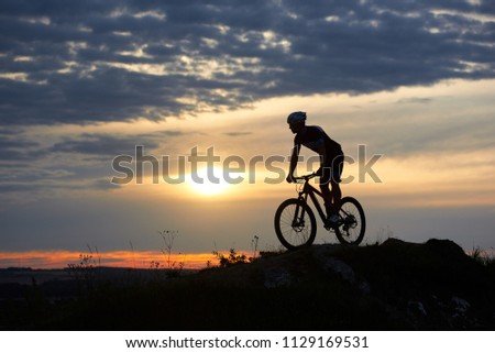 Silhouette of male cyclist wearing a helmet and sports clothes riding a mountain bike on rocks in the mountains against a beautiful sunset with a bright sun and sky in the clouds. #1129169531