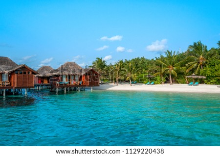 The perfect beach. Water bungalow. Luxury escape. Tropical paradise. Honeymoon at Maldives. Palms and white sund. Blue ocean #1129220438