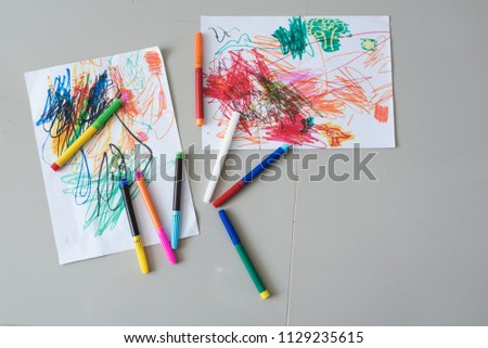 Top view on child's drawings and colorful paints. Painting Abstract Design using Various Colors on drawing on paper and early learning.Education concept. #1129235615