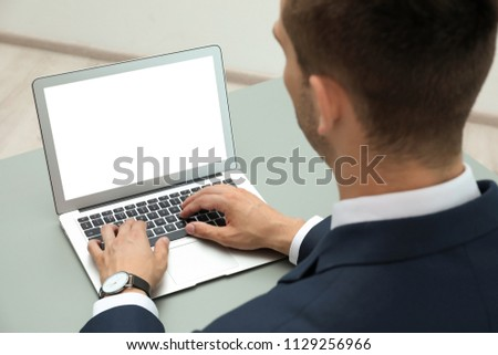 Man in office wear using laptop at table indoors #1129256966