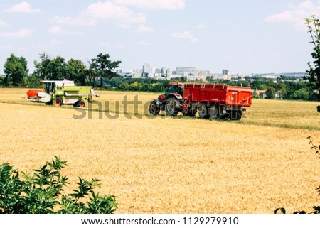 Bezannes France july 07, 2018 View of a tractor working in the field in Champagne area in the afternoon #1129279910