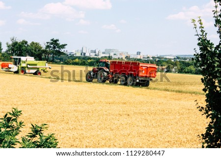 Bezannes France july 07, 2018 View of a tractor working in the field in Champagne area in the afternoon #1129280447