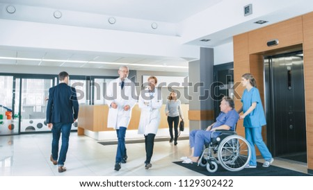 First Floor of the Busy Hospital, Doctors, Nurses and Personnel Busy Working, Assistant Moves Elderly Man in the Wheelchair. New Modern Medical Hospital with Professional Staff. #1129302422
