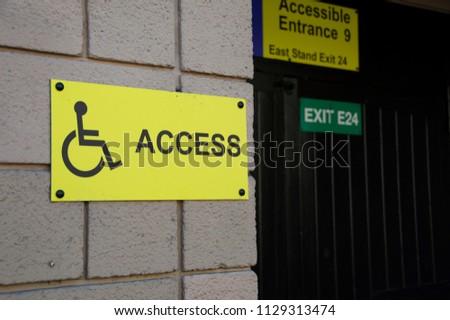 Yellow Wheelchair Access Sign At Stadium #1129313474