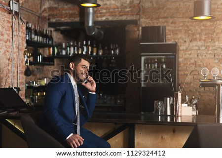 Cheerful business talking on phone, sitting at bar counter, having successful and pleasant conversation, copy space #1129324412