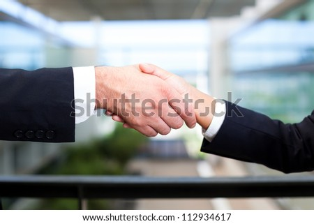 Man and woman shaking hands in office environment #112934617