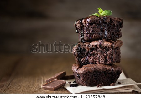 A stack of chocolate brownies on wooden background with mint leaf on top, homemade bakery and dessert #1129357868