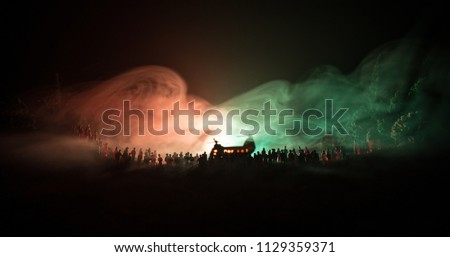 Military helicopter ready to fly from conflict zone or Silhouettes of a large crowd of people trying to escape with helicopter. Decorated night installed photo with foggy toned backlit #1129359371