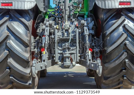 Tractor for farm work, modern agricultural transport working in the field, modern tractor close-up #1129373549