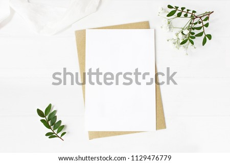 Feminine wedding stationery, desktop mock-up scene. Blank greeting card, craft envelope, baby's breath flowers, silk ribbon and lentisk branches. Old white wooden table background. Flat lay, top view. #1129476779
