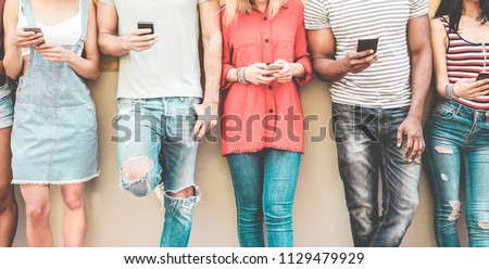 Group of millennial friends watching smart mobile phones - Teenagers addiction to new technology trends - Concept of youth, tech, social and friendship - Focus on smartphones hands #1129479929