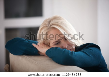 Sad depressed woman at home sitting on the couch, looking down and touching her forehead, loneliness and pain concept #1129486958