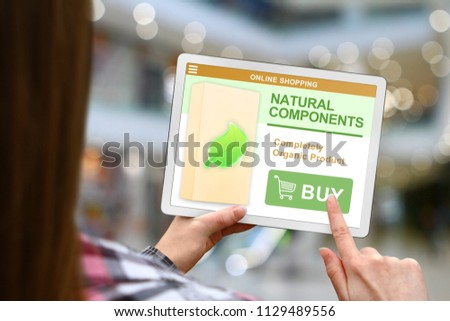 Natural components concept, girl with tablet pc on blurred mall background #1129489556
