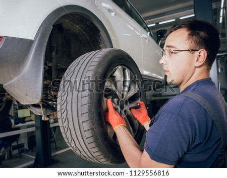 Car mechanic inspecting wheel and suspension detail of lifted automobile at repair service station. Auto service. #1129556816
