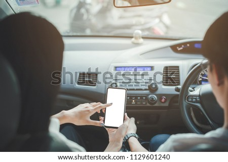 Hipster man looking on navigation map in car, tourist traveler driving and holding in male hands smartphone gps with clean screen display, panoramic view way road, trip in transportation from window #1129601240