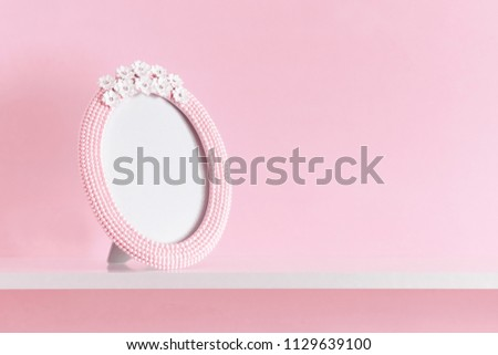 Beautiful pink blank photo frame on the shelf with copy space. Pink background.