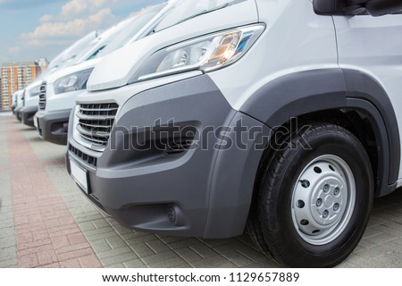 number of new white minibuses and vans outside #1129657889