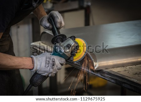 Milan, Italy - June 14 2018: metalworking worker at the milling bench of mechanical parts in steel after flame welding, in the Milan factory #1129675925