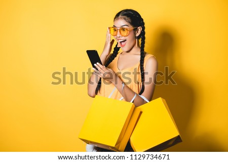 Beautiful young woman with shopping bags using her smart phone on yellow background.Shopaholic shopping Fashion. #1129734671