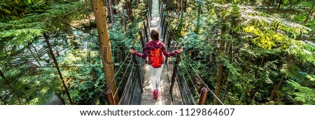 Canada travel people lifestyle banner. Tourist woman walking in famous attraction Capilano Suspension Bridge in North Vancouver, British Columbia, canadian vacation destination for tourism. Royalty-Free Stock Photo #1129864607