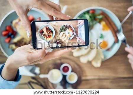 Close up of woman taking photo of delicious breakfast in restaurant. Couple eating together