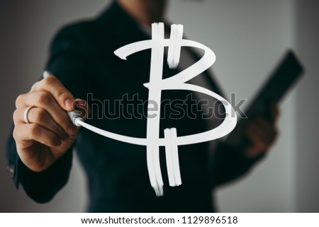 Writing hand. Business woman holds pen or marker and writing Bitcoin symbol #1129896518