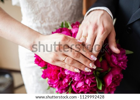 Hands of the groom and bride with rings and bridal bouquet #1129992428
