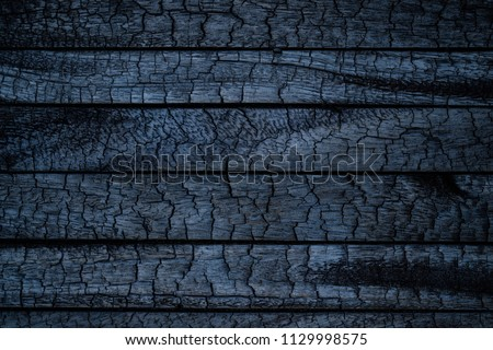 BBQ background. Burnt wooden Board texture. Burned scratched hardwood surface. Smoking wood plank background. Burned wooden grunge texture #1129998575