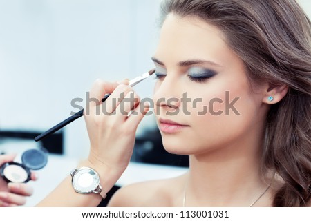 Make-up artist applying bright base color eyeshadow on model's eye and holding a shell with eyeshadow on background, close up #113001031
