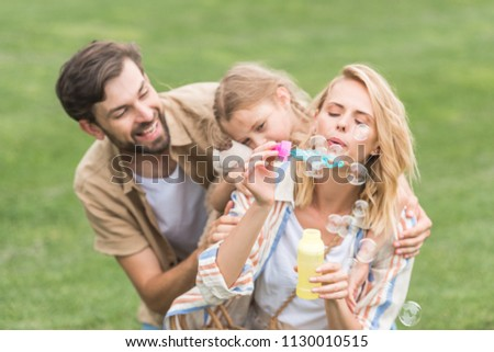 happy family with one child having fun together and blowing soap bubbles in park  #1130010515