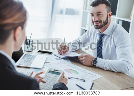 smiling financiers looking at each other during work in office #1130033789