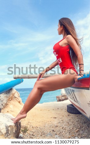 Seductive woman in red swimsuit at the sunny beach of Bali island,Indonesia #1130079275