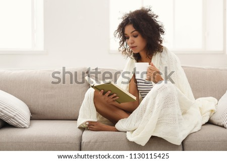 Thoughtful african-american student girl reading book. Young woman studying at home, sitting on beige couch wrapped up in white blanket and holding coffee cup, copy space #1130115425