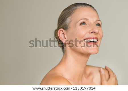 Portrait of a cheerful senior woman smiling while looking away isolated on gray background. Happy mature woman after spa massage and anti-aging treatment on face. Royalty-Free Stock Photo #1130197814
