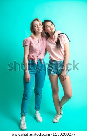 portrait of young different nationalities teenage girlfriends, caucasian woman and Asian woman - hagging, isolated over blue background. European woman holding a small yellow dumbbell in one hand. #1130200277