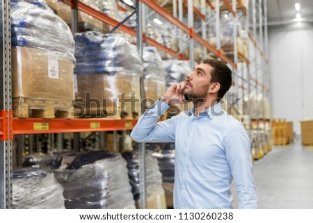 wholesale, logistic business, technology and people concept - businessman calling on smartphone at warehouse #1130260238