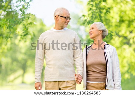 old age and people concept - happy senior couple holding hands over green natural background #1130264585