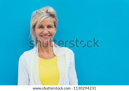 Happy vivacious older blond woman in a colorful yellow top posing against a bright blue wall with copy space