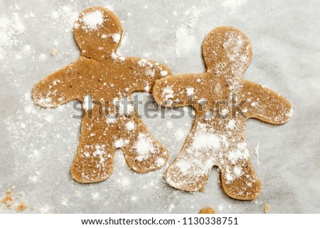 Preparation of ginger biscuits. Cutting figured cookies in the form of gingerbread man.  New Year's Eve symbol. #1130338751