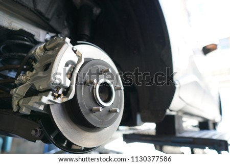 Close up of Brake Disc of the vehicle for repair.Automobile mechanic in process of new tire replacement.Car brake repairing in garage.Car Service and technician concept. Royalty-Free Stock Photo #1130377586