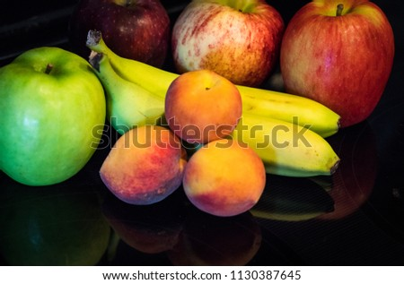 A collection of organic fruits on black mirrored reflection surface , local organic Texas peaches , with apples and bananas #1130387645