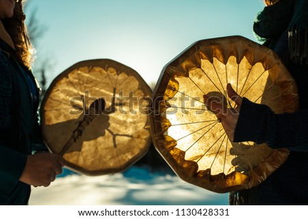 Women holding and playing their sacred drums outdoors in the wintertime #1130428331