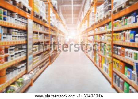 Hardware construction supermarket aisle and shelves. Perspective view of hypermarket rows with products. Blurred abstract shopping and trading background #1130496914