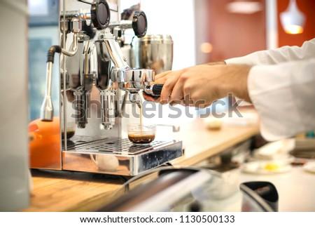 Detail of man's hand preparing coffee with coffee machine #1130500133