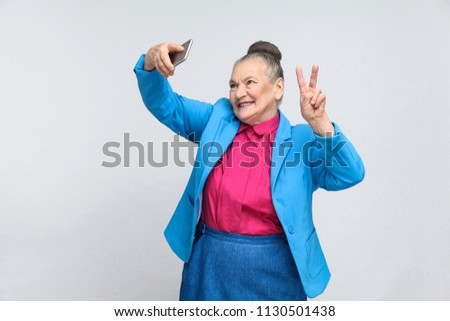 aged woman making selfie with peace sing and smilling. Portrait of handsome expressive grandmother in light blue suit with collected gray hair bun hairstyle. Studio shot, isolated on gray background